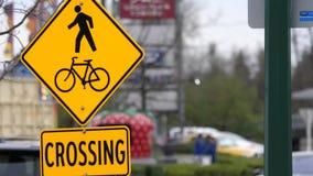 Κίνηση των ανθρώπων και του ποδηλάτου που διασχίζει το σημάδι στο πεζοδρόμιο με την κυκλοφοριακή ροή θαμπάδων φιλμ μικρού μήκους
