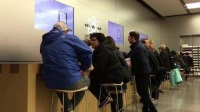 Κίνηση των ανθρώπων που έχουν κάποια υπηρεσία στο φραγμό μεγαλοφυίας μέσα στο κατάστημα της Apple απόθεμα βίντεο