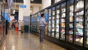 Κίνηση των ανθρώπων που αγοράζουν τα τρόφιμα μέσα στο έξυπνο κατάστημα τροφίμων τιμών φιλμ μικρού μήκους