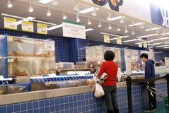 Κίνηση των ανθρώπων που αγοράζουν τα ψάρια στο τμήμα θαλασσινών μέσα στην υπεραγορά T&T Στοκ Φωτογραφίες