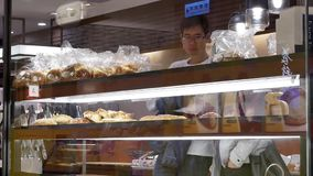 Κίνηση των ανθρώπων που δοκιμάζουν το ψωμί δειγμάτων μέσα στο κινεζικό κατάστημα κέικ και ψωμιού απόθεμα βίντεο