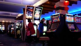 Κίνηση των ανθρώπων που παίζουν το μηχάνημα τυχερών παιχνιδιών με κέρματα μέσα στη χαρτοπαικτική λέσχη