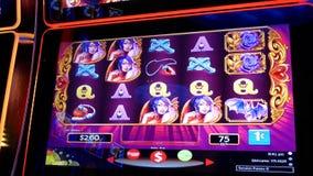 Κίνηση των ανθρώπων που παίζουν το μηχάνημα τυχερών παιχνιδιών με κέρματα μέσα στη χαρτοπαικτική λέσχη απόθεμα βίντεο