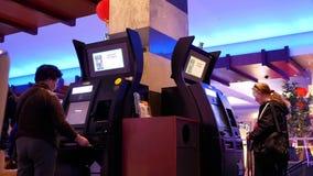 Κίνηση των ανθρώπων που παρεμβάλλουν την κερδίζοντας απόδειξη στη μηχανή στα χρήματα μετρητών έξω φιλμ μικρού μήκους