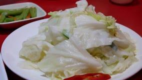 Κίνηση των ανθρώπων που τρώνε το τηγανισμένο λάχανο στον πίνακα μέσα στο κινεζικό εστιατόριο απόθεμα βίντεο