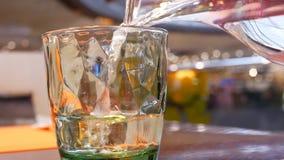 Κίνηση των ανθρώπων που χύνουν τα νερά πηγής στο γυαλί μέσα στο κινεζικό εστιατόριο απόθεμα βίντεο