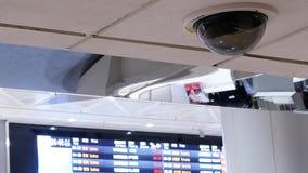 Κίνηση των κάμερων ασφαλείας μπροστά από τον πίνακα προγραμμάτων πτήσης μέσα στο διεθνή αερολιμένα Taoyuan απόθεμα βίντεο