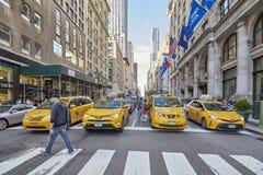 Κίτρινα αμάξια που περιμένουν μπροστά από ένα για τους πεζούς πέρασμα κατά τη διάρκεια της ώρας κυκλοφοριακής αιχμής Στοκ Εικόνες