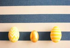 Κίτρινα αυγά Πάσχας στο ριγωτό υπόβαθρο με την αναδρομική επίδραση φίλτρων στοκ εικόνα