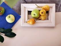 Κίτρινα αχλάδια και μήλα σε ένα άσπρο πλαίσιο, φθινόπωρο, διακοσμητική σύνθεση σε ένα ελαφρύ υπόβαθρο στοκ εικόνα