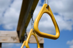 Κίτρινα δαχτυλίδια φραγμών πιθήκων που κρεμούν από το σύνολο παιδικών χαρών Στοκ Φωτογραφία