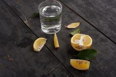 Κίτρινα λεμόνια, φύλλα και ποτήρι του νερού Στοκ εικόνα με δικαίωμα ελεύθερης χρήσης