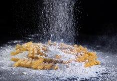 Κίτρινα ιταλικά ζυμαρικά, μακαρόνια στο αλεύρι στο απομονωμένο ο Μαύρος κλίμα στοκ φωτογραφία