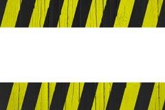 Κίτρινα και μαύρα λωρίδες προειδοποιητικών σημαδιών που χρωματίζονται πέρα από το ραγισμένο ξύλο ως πλαίσιο συνόρων Στοκ εικόνες με δικαίωμα ελεύθερης χρήσης