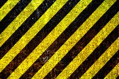 Κίτρινα και μαύρα λωρίδες προειδοποιητικών σημαδιών που χρωματίζονται πέρα από το σκουριασμένο μεταλλικό πιάτο ως υπόβαθρο σύστασ Στοκ Εικόνες