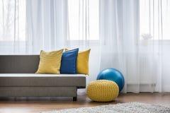 Κίτρινα και μπλε μαξιλάρια στον καναπέ Στοκ εικόνα με δικαίωμα ελεύθερης χρήσης