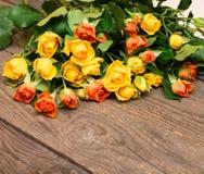 Κίτρινα και πορτοκαλιά τριαντάφυλλα σε ένα ξύλινο υπόβαθρο Ημέρα Women s, Va Στοκ Φωτογραφία