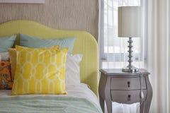 Κίτρινα και πράσινα και μαξιλάρια σχεδίων στο κλασικό κρεβάτι ύφους Στοκ εικόνα με δικαίωμα ελεύθερης χρήσης