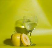 Κίτρινα μήλα ενός στα πράσινα υποβάθρου με ένα ποτήρι του νερού Στοκ φωτογραφία με δικαίωμα ελεύθερης χρήσης