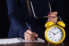 Κίτρινα παλαιά αναδρομικά αναλογικά ρολόι και κορίτσι συναγερμών στο γράψιμο υποβάθρου στοκ φωτογραφία