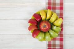 Κίτρινα, πράσινα και κόκκινα διαιρεμένα στα τέσσερα μήλα που σχεδιάζονται γύρω από ολόκληρο το μήλο σε ένα πιατάκι Στοκ φωτογραφία με δικαίωμα ελεύθερης χρήσης