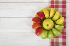 Κίτρινα, πράσινα και κόκκινα διαιρεμένα στα τέσσερα μήλα που σχεδιάζονται γύρω από ολόκληρο το μήλο σε ένα πιατάκι Στοκ φωτογραφίες με δικαίωμα ελεύθερης χρήσης