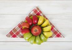 Κίτρινα, πράσινα και κόκκινα διαιρεμένα στα τέσσερα μήλα που σχεδιάζονται γύρω από ολόκληρο το μήλο σε ένα πιατάκι Στοκ εικόνες με δικαίωμα ελεύθερης χρήσης