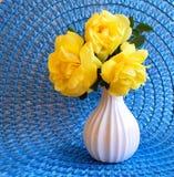 Κίτρινα τριαντάφυλλα Floribunda τρίο κινηματογραφήσεων σε πρώτο πλάνο στο μπλε χαλί στοκ φωτογραφίες