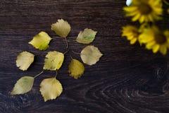 Κίτρινα φύλλα φθινοπώρου σε ένα ξύλινο υπόβαθρο Στοκ Φωτογραφία