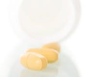 Κίτρινα χάπια που ανατρέπονται από το μπουκάλι που απομονώνεται στο άσπρο υπόβαθρο Στοκ Φωτογραφία