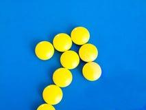 Κίτρινα χάπια σε ένα μπλε υπόβαθρο Στοκ εικόνα με δικαίωμα ελεύθερης χρήσης