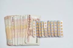 Κίτρινα χάπια στα φύλλα αλουμινίου και τραπεζογραμμάτια χρημάτων στην απομονωμένη λευκιά ΤΣΕ στοκ φωτογραφία με δικαίωμα ελεύθερης χρήσης
