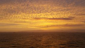 Κίτρινα χρυσά σύννεφα σε όλο τον ουρανό κατά τη διάρκεια ενός ηλιοβασιλέματος στοκ εικόνα