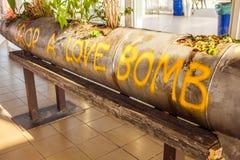 Κίτρινα χρώμα & x22 επιγραφής Ρίξτε μια αγάπη bomb& x22  στο κρεβάτι λουλουδιών της περίπτωσης του πυραύλου αέρα Στοκ φωτογραφία με δικαίωμα ελεύθερης χρήσης