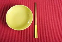 Κίτρινα chopsticks και κύπελλο στο κόκκινο χαλί ρύθμισης επιτραπέζιων θέσεων Στοκ εικόνες με δικαίωμα ελεύθερης χρήσης