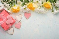 Κίτρινα daffodils με τα άσπρα crisands και ένα δώρο με τα σπιτικά μπισκότα υπό μορφή καρδιών, σε ένα ξύλινο υπόβαθρο, τοπ άποψης, στοκ εικόνες