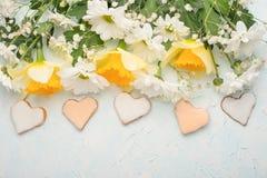 Κίτρινα daffodils με τα άσπρα crisands και μπισκότα υπό μορφή καρδιών σε ένα ξύλινο υπόβαθρο, τοπ άποψη, με το κενό διάστημα για  στοκ φωτογραφίες με δικαίωμα ελεύθερης χρήσης