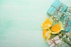 Κίτρινα daffodils με τα δώρα σε ένα ξύλινο υπόβαθρο, τοπ άποψη, με το κενό διάστημα για το γράψιμο ή τη διαφήμιση στοκ εικόνες με δικαίωμα ελεύθερης χρήσης