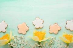 Κίτρινα daffodils με τα μπισκότα σε ένα ξύλινο υπόβαθρο, τοπ άποψη, με το κενό διάστημα για το γράψιμο ή τη διαφήμιση στοκ φωτογραφίες με δικαίωμα ελεύθερης χρήσης