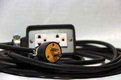 Κίτρινες βούλωμα και έξω έξοδος εστίασης με το μαύρο καλώδιο στο άσπρο υπόβαθρο Χρησιμοποιημένος για την ηλεκτρική σύνδεση στοκ εικόνες
