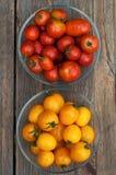 Κίτρινες και κόκκινες ντομάτες στην ξύλινη επιφάνεια στοκ φωτογραφία