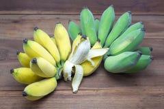 Κίτρινες και πράσινες μπανάνες στο ξύλινο υπόβαθρο, εδώδιμα φρούτα Στοκ Εικόνες