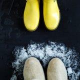 Κίτρινες λαστιχένιες μπότες μπροστά από τις μπότες χιονιού και λειώνοντας χιόνι στο μαύρο υπόβαθρο Στοκ Εικόνες