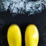 Κίτρινες λαστιχένιες μπότες μπροστά από το λειώνοντας χιόνι Στοκ εικόνες με δικαίωμα ελεύθερης χρήσης