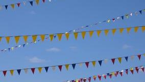 Κίτρινες, μπλε, άσπρες και κόκκινες σημαίες τριγώνων για το κόμμα καρναβαλιού στο υπόβαθρο ουρανού Άνευ ραφής υπόβαθρο βρόχων απόθεμα βίντεο