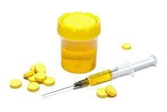 Κίτρινες ταμπλέτες, εμβόλιο και σύριγγα με το εμβόλιο του κίτρινου χρώματος Στοκ Φωτογραφία