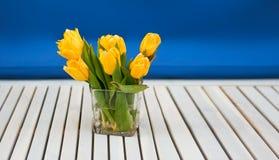 Κίτρινες τουλίπες στο βάζο γυαλιού στον άσπρο ξύλινο πίνακα και το μπλε υπόβαθρο Στοκ Φωτογραφίες