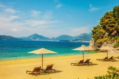 Κίτρινη αμμώδης παραλία με τους αργοσχόλους ήλιων μια ηλιόλουστη ημέρα Αιχμές βουνών ορατές στην απόσταση πίσω ανασκόπησης όμορφη στοκ εικόνα με δικαίωμα ελεύθερης χρήσης