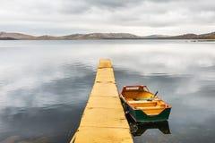 Κίτρινη αποβάθρα και κίτρινη βάρκα στη λίμνη Στοκ Εικόνες