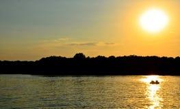 Κίτρινη βάρκα ακτίνων ήλιων θερινού ηλιοβασιλέματος ποταμών στον ποταμό Στοκ Φωτογραφίες